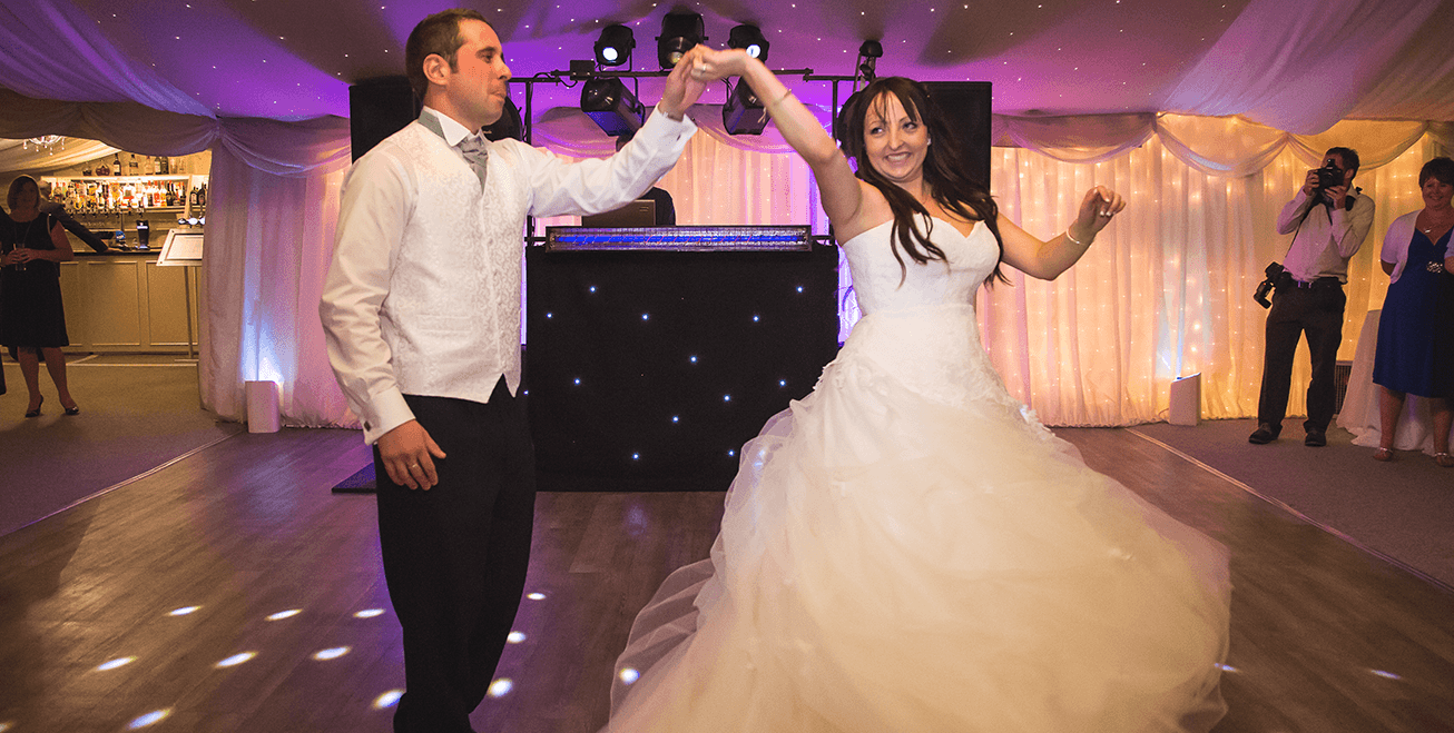 bride and groom dancing and holding hands
