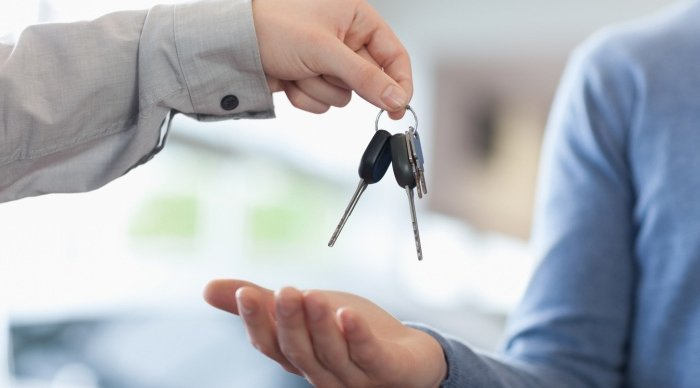 car salesman handing keys over to new car owner