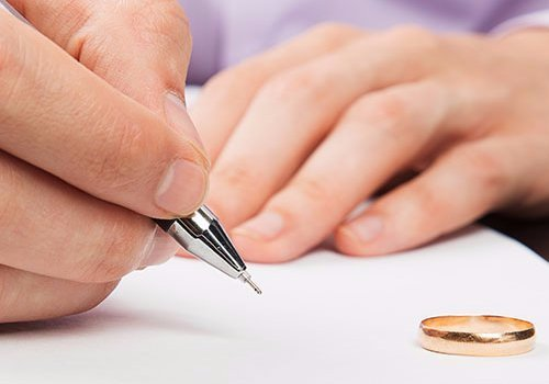 Closeup of male hand signing divorce papers and using family law services in Cape Girardeau, MO