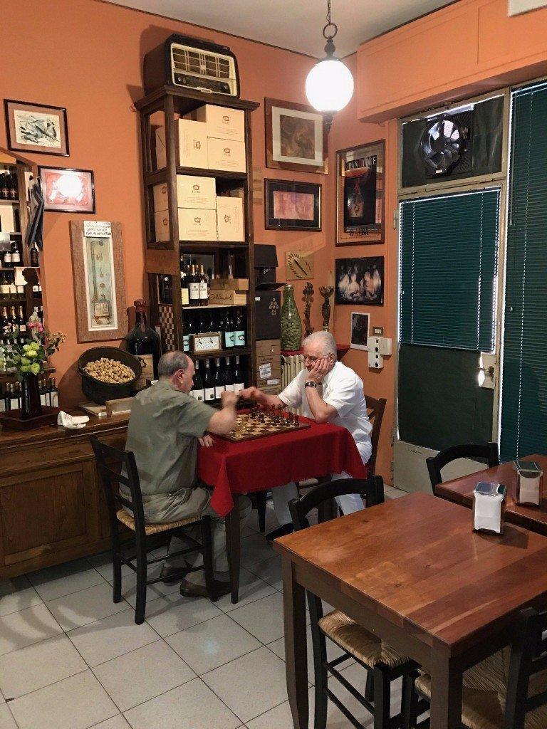 due anziani che giocano a scacchi nell'enoteca