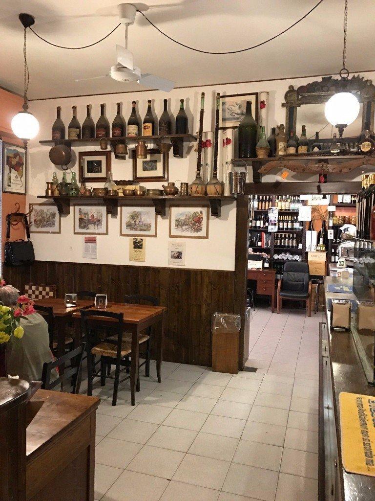 tavoli dell'enoteca con esposizione vini in vista