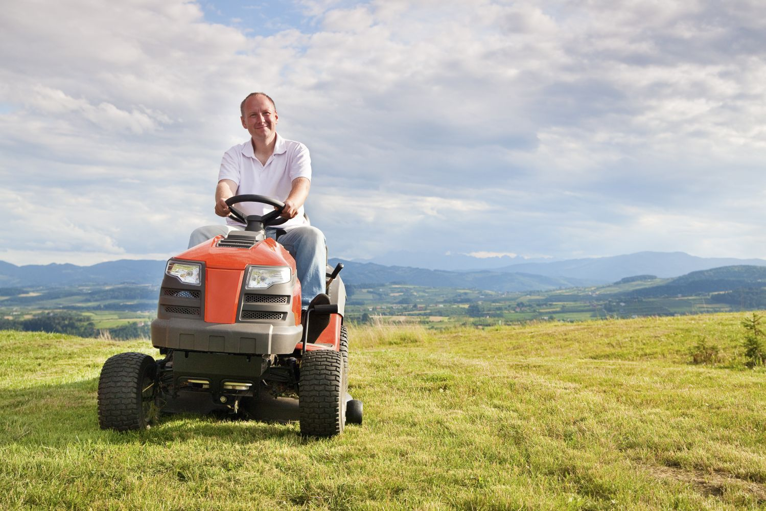 Man working after ride on mower repairs in Green Island