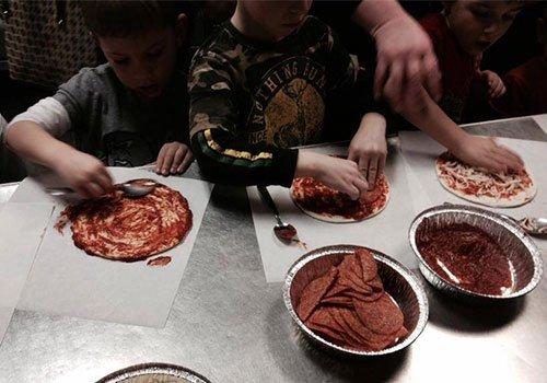 Children preparing pizza and pasta at our pizzeria in Hamilton