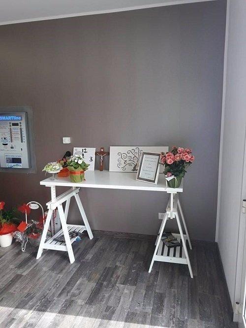 un tavolo con cornici e vasi di fiori