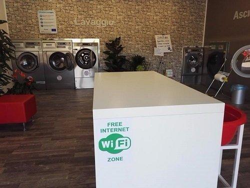 interno di una lavanderia con vista delle lavatrici e un bancone con scritto Wifi zone