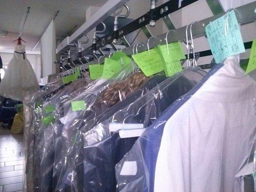 degli appendini con degli abiti lavati in una lavanderia