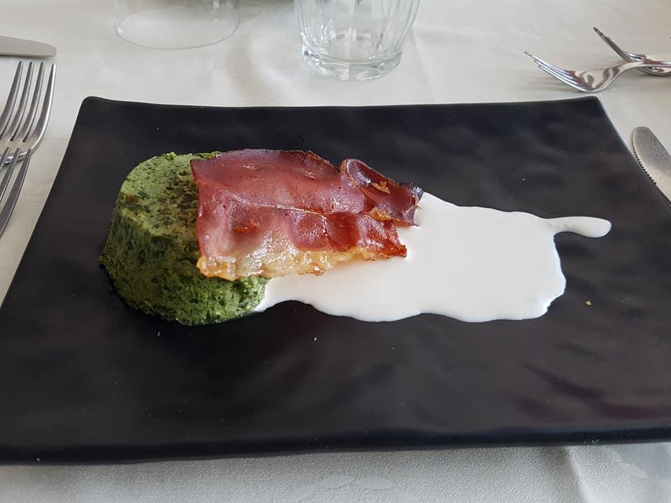 un piatto con un tortino verde e dello speck