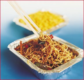 Chopsticks picking up food from a noodle based Chinese meal in a takeaway foil container