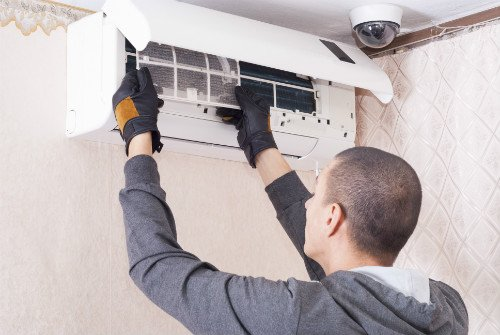 Heating and cooling specialist repairing the air conditioner in Honeoye Falls, NY