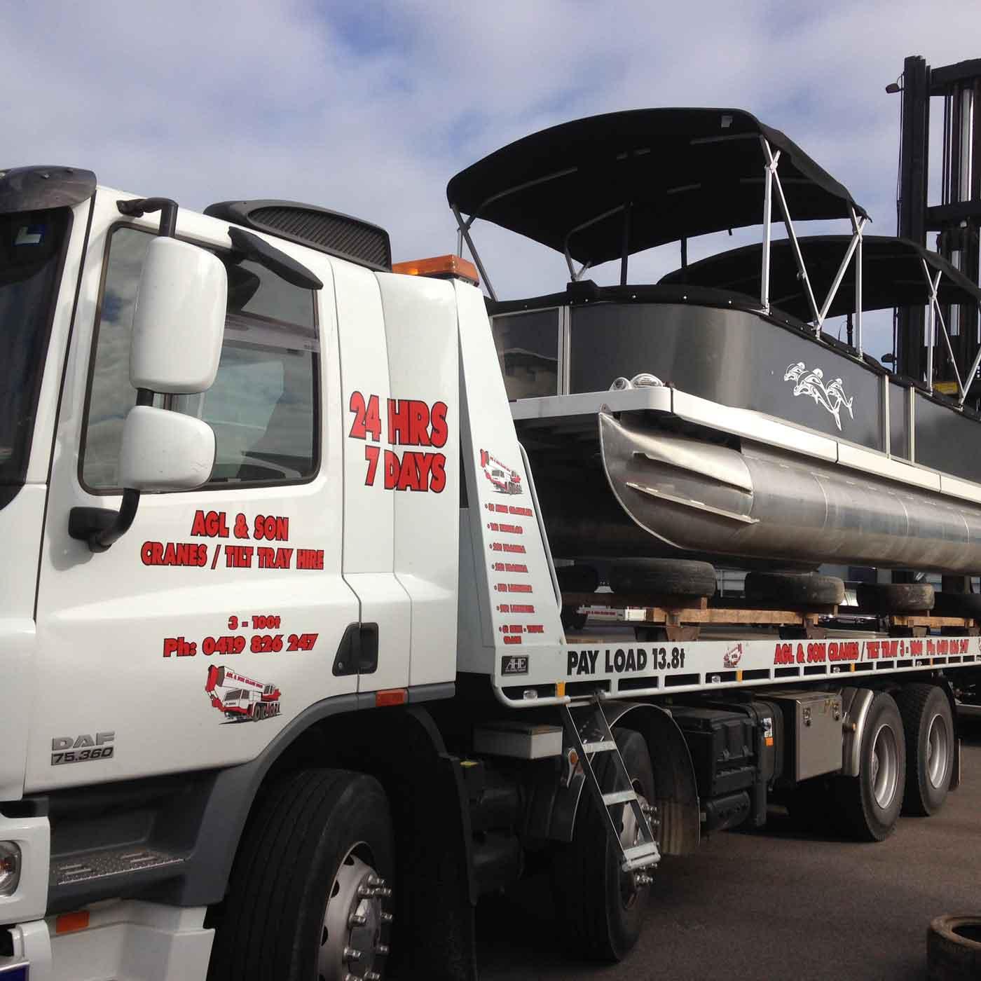 tilt truck hauling a pontoon boat