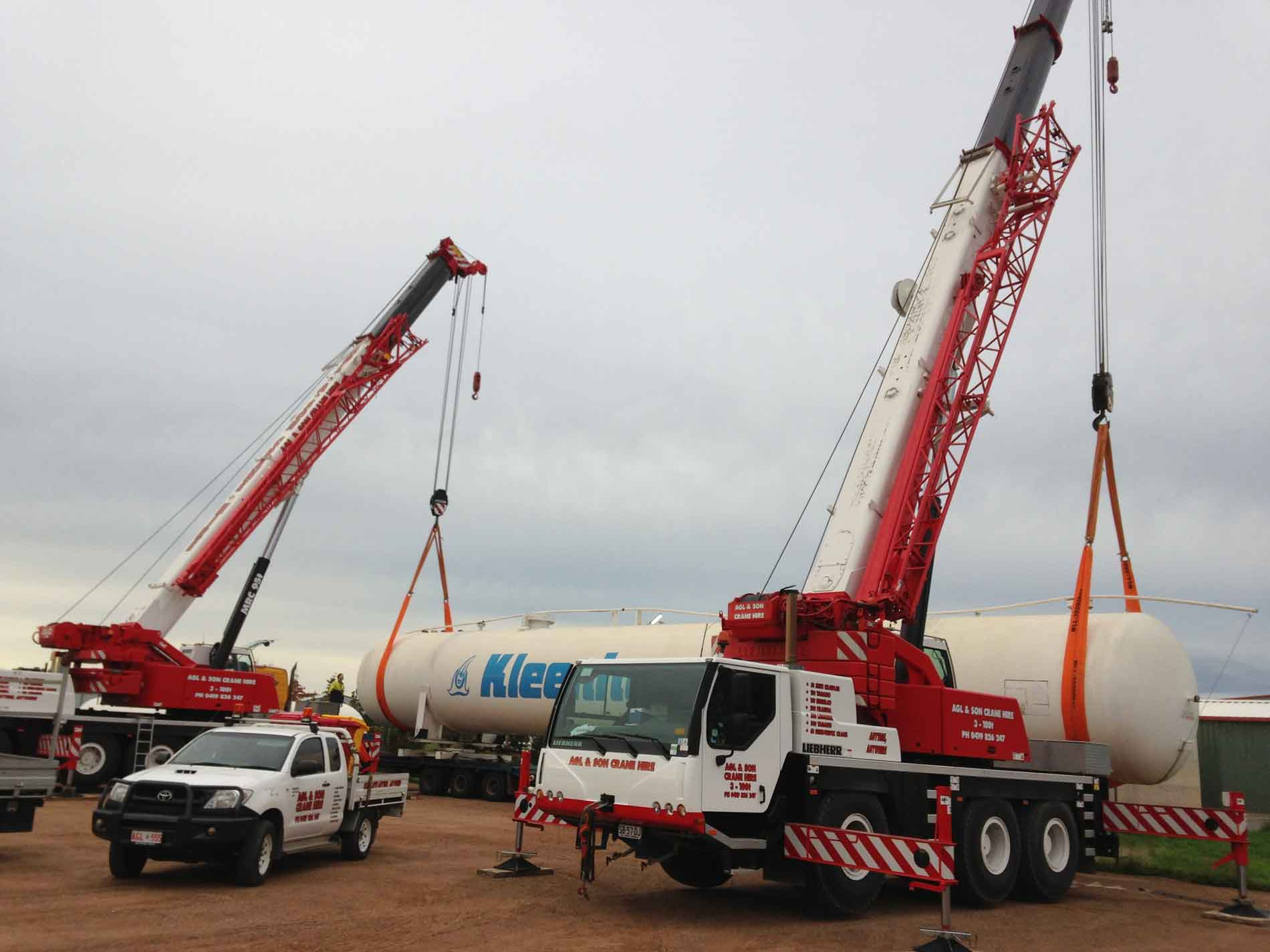 two red cranes lifting giant pipe