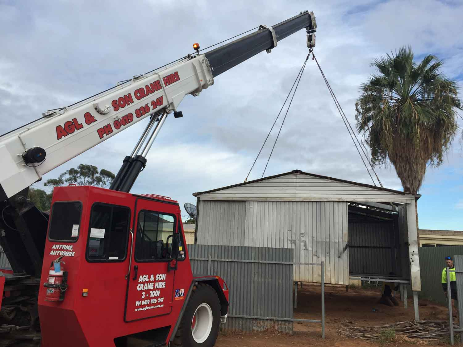 crane picking up shed