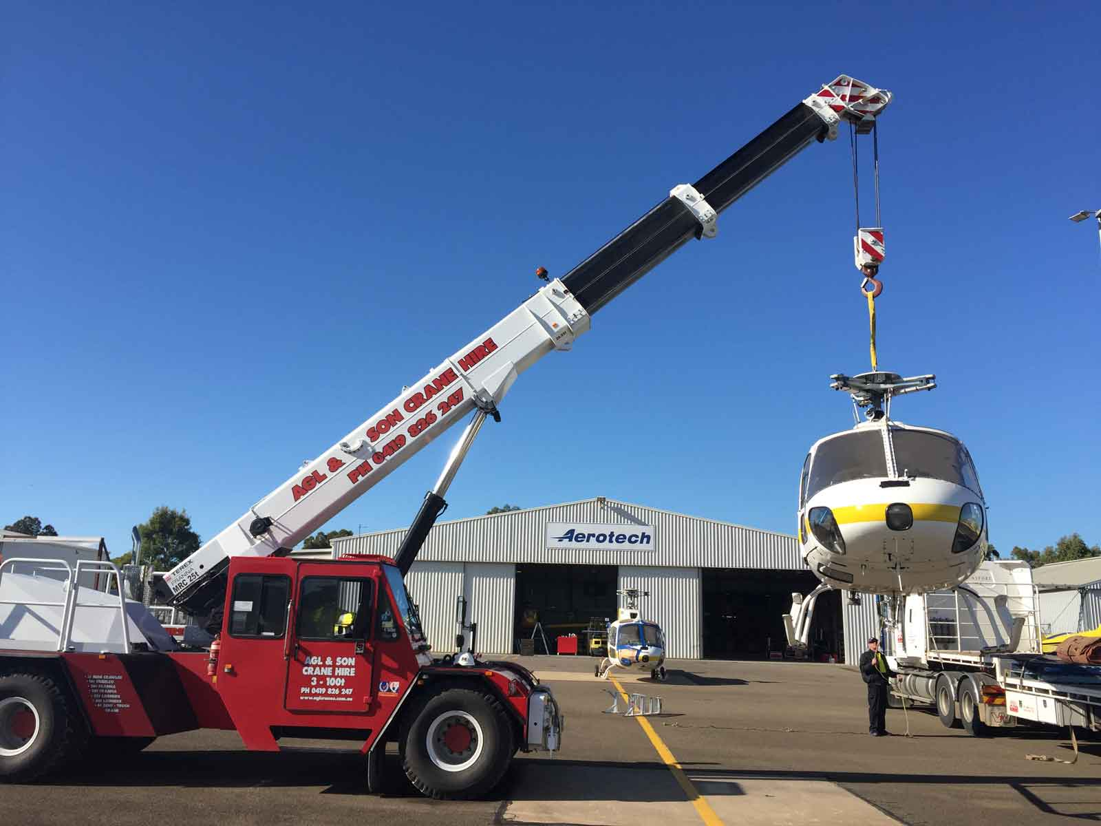 red crane lifting a helicopter