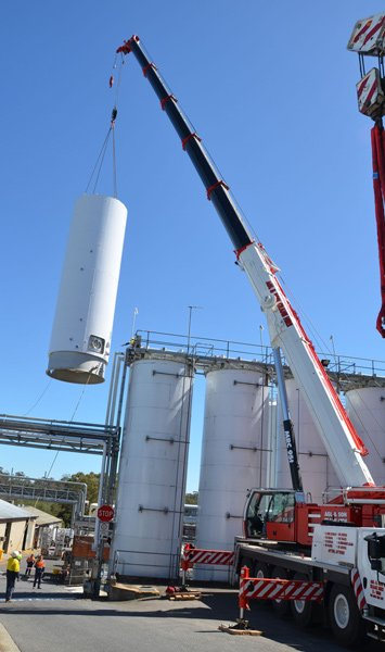 crane lifting white cylinder