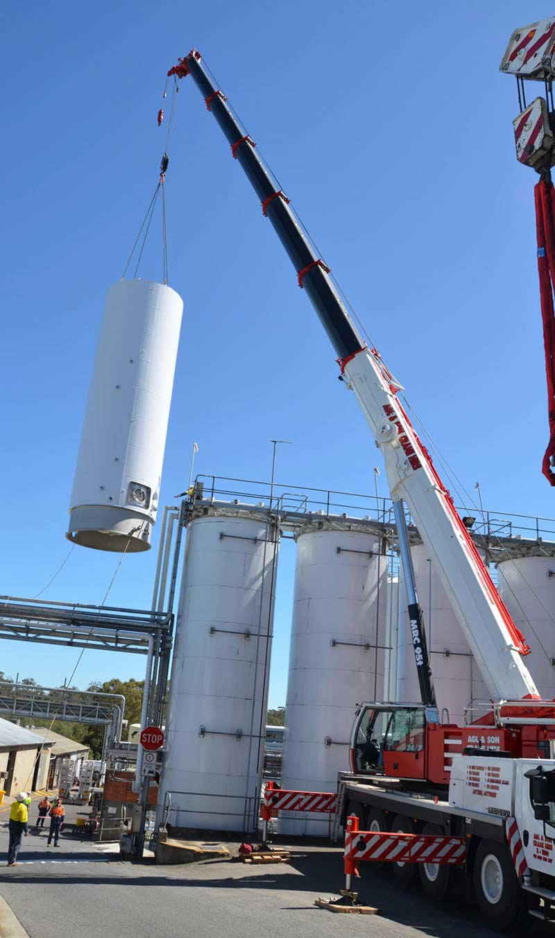 installing white cylinder with a crane