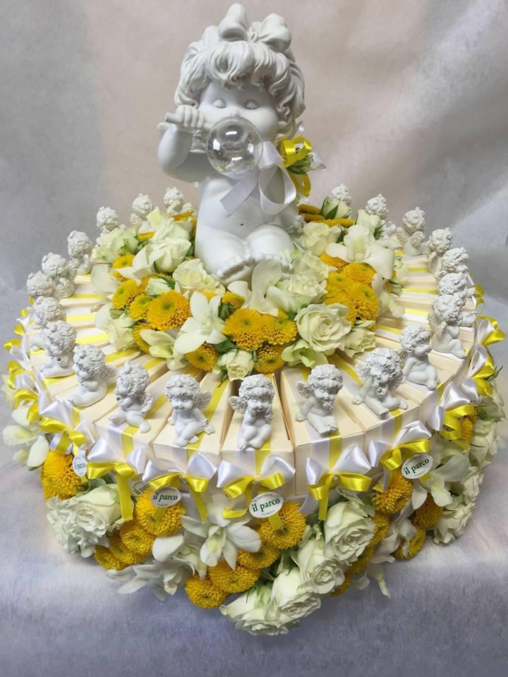 delle confezioni con delle bomboniere disposte a formare una torta e sopra una statuetta di una bambina