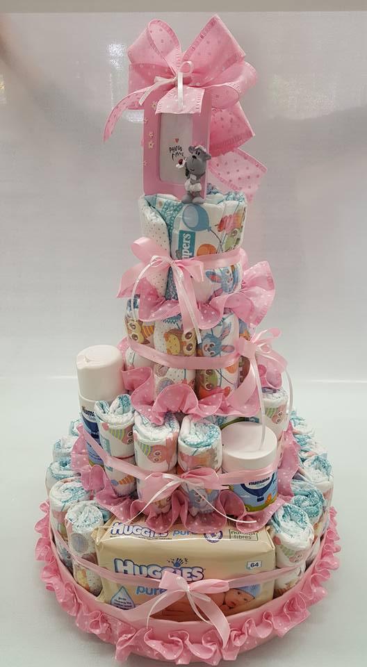dei pannolini per bambino disposti a formare una torta a quattro piani e dei fiocchi rosa