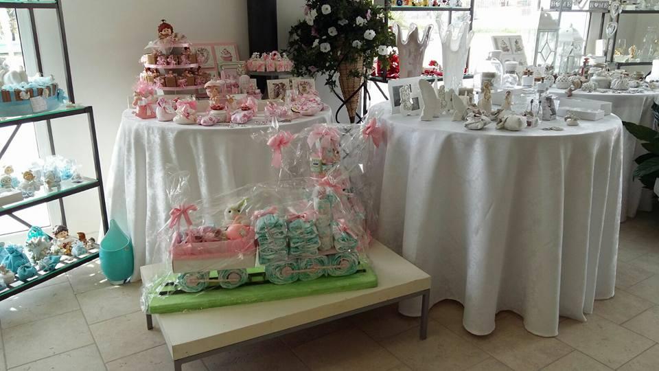 dei tavoli con sopra delle bomboniere blu e rosa per bambini