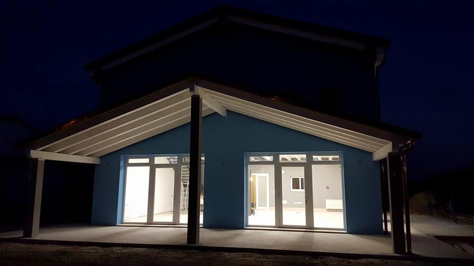 una casa blu con una specie di gazebo in legno davanti