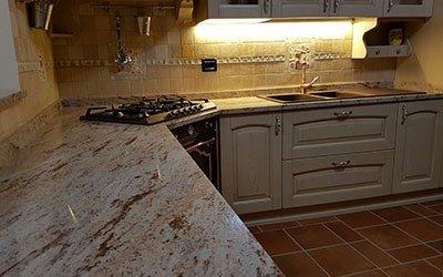 Originale cucina con controsoffitto di marmo marrone venato