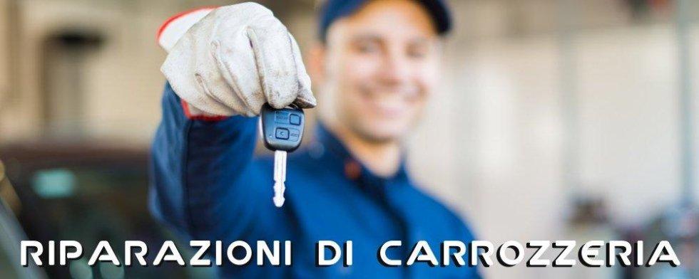 meccanico sorridente porge delle chiavi di un automobile