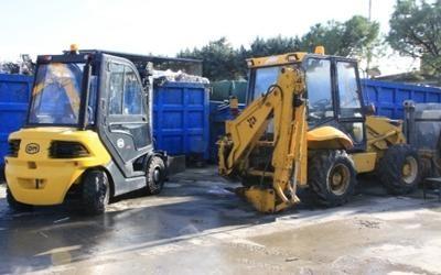 un muletto, una scavatrice e dei container cion dei rifiuti
