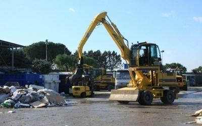 un mezzo da lavoro, dei rifiuti e dei container