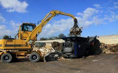 un mezzo da lavoro che sta demolendo dei rifiuti con un braccio meccanico