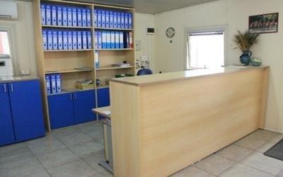 un bancone di una reception di un ufficio e dietro uno scaffale con dei raccoglitori