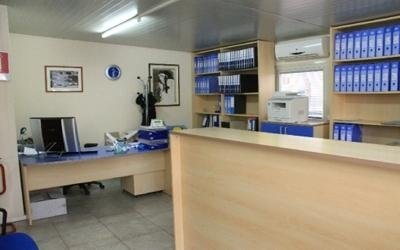 un bancone, uno scaffale con dei raccoglitori e una scrivania