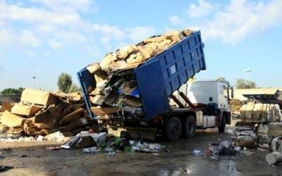 un camion che sta scaricando delle scatole di cartone con dei rifiuti