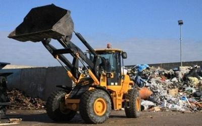 un mezzo da lavoro e dei rifiuti in una discarica