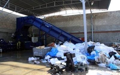 dei rifiuti dentro a dei sacchetti all'interno di un capannone di una discarica
