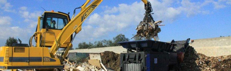 una mezzo demolitore che demolisce della ferraglia