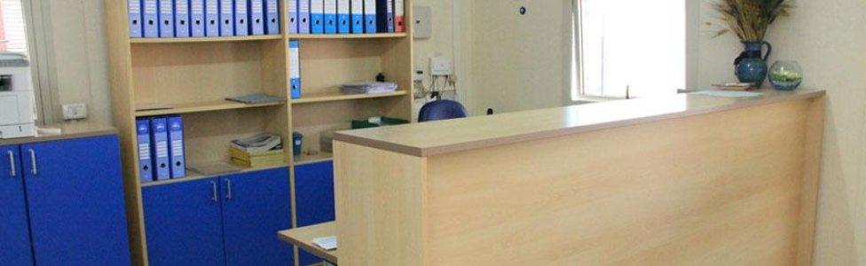 una scrivania in legno alta e una libreria con dei raccoglitori