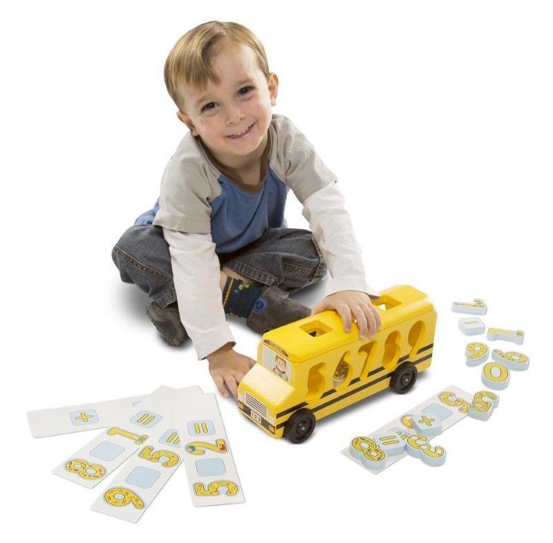 un bambino con uno scuolabus giocattolo e dei numeri