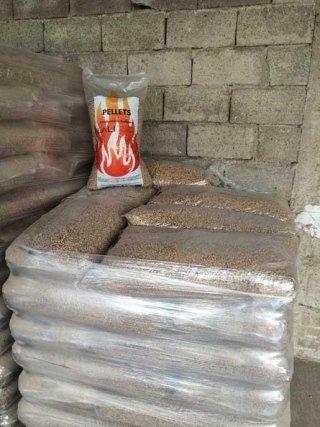 Una serie di sacchi di pellet di plastica con dei pellet e sopra un'altro sacchettino con una fiamma disegnata