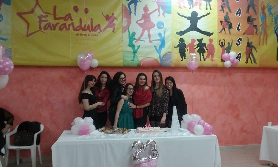 delle ragazze davanti a un tavolo con una torta di compleanno