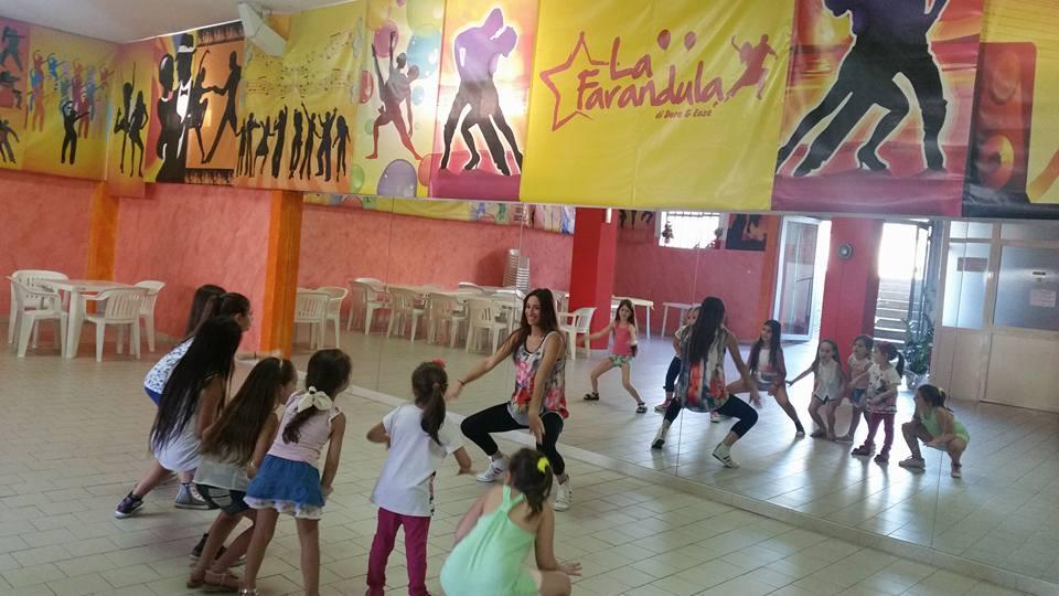 una sala con specchi su un muro e una ragazza mentre insegna a  ballare ai dei bambini