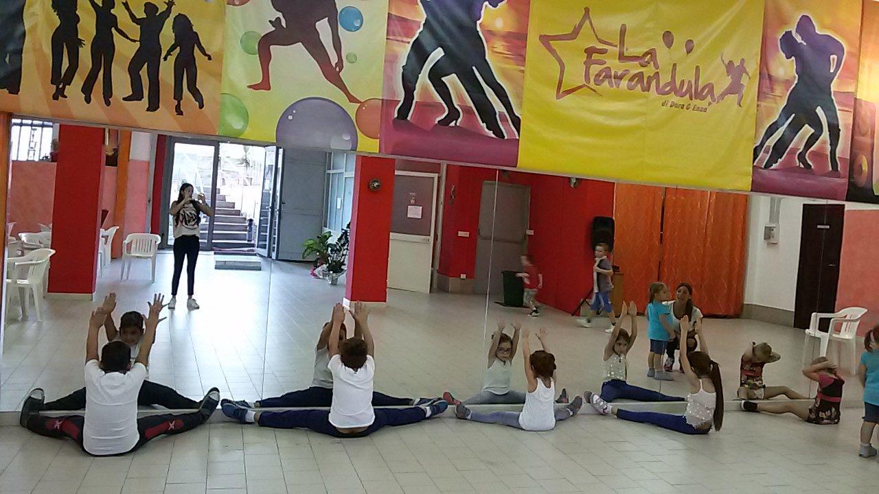 Dei bambini mentre fanno stretching davanti a degli specchi