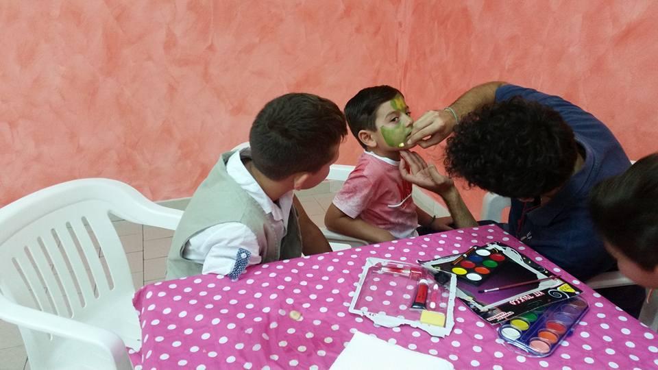 un uomo mentre dipinge il viso di un bambino