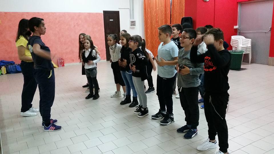 Dei bambini in piedi davanti a  due insegnanti di ballo