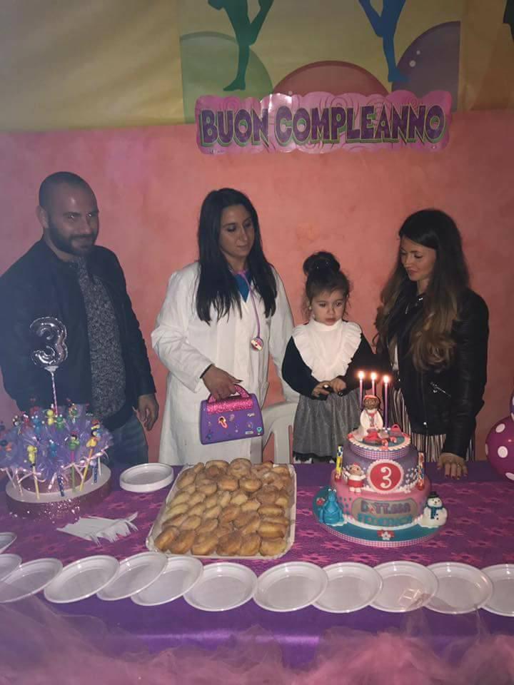 una bambina davanti a una torta con numero 3 e accanto dei pasticcini sul tavolo