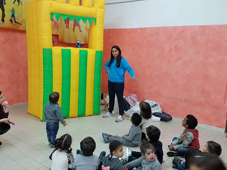 una ragazza in piedi, dei bambini seduti e sulla destra una struttura di gomma con un pupazzo