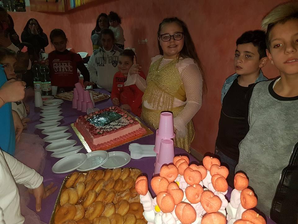 una bambina davanti un tavolo con una torta di color rosa e altri dolci e accanto altri bambini in piedi