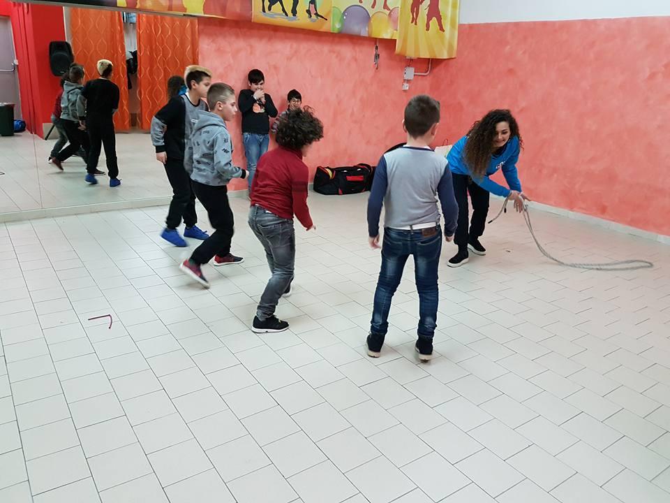una donna mentre fa giocare dei bambini con una corda