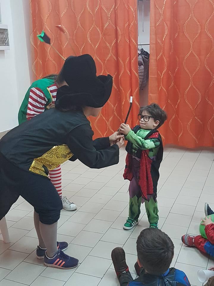 due ragazze che danno una bacchetta a un bambino in costume