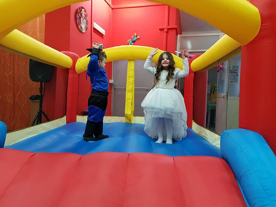 un bambino e una bambina che ballano su una struttura di gomma colorata
