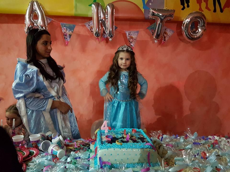 una ragazza e una bambina vestite da principesse e davanti una torta