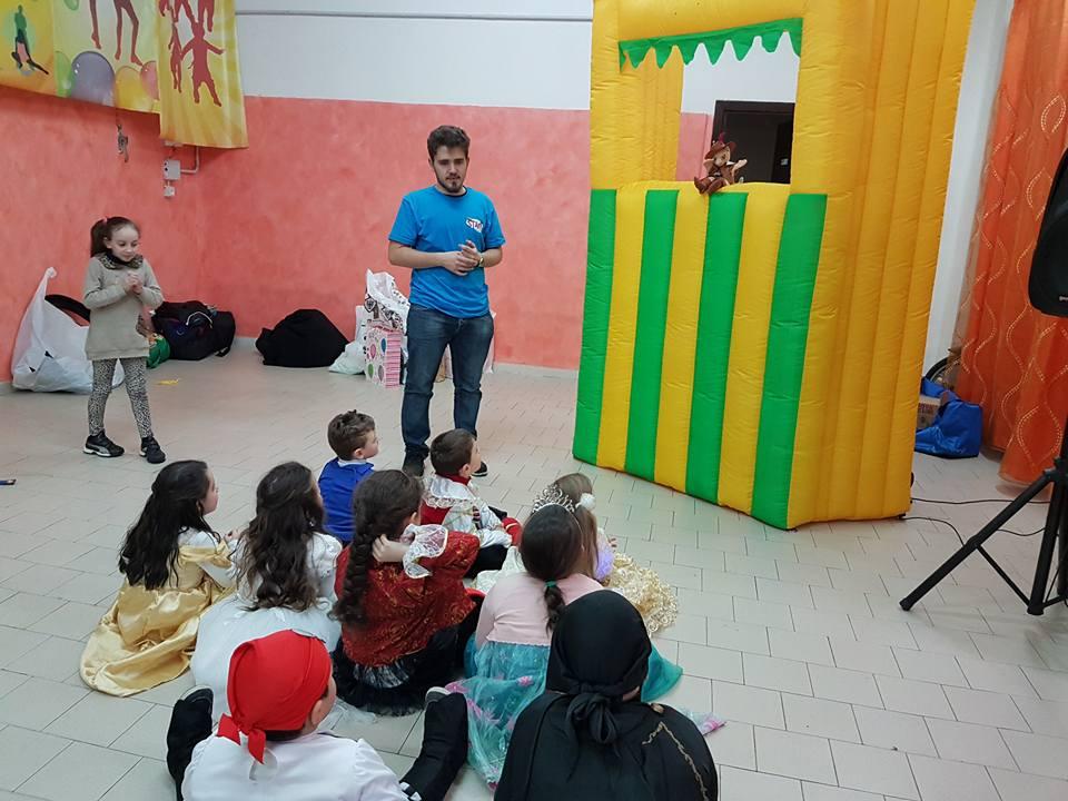 un ragazzo in piedi, dei bambini seduti e sulla destra una struttura di gomma con un pupazzo